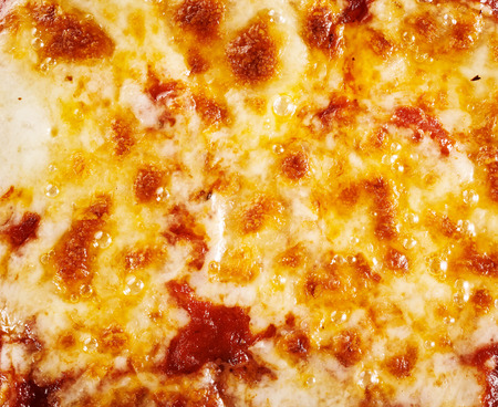 pizza base: Background texture of melted mozzarella cheese on a pizza base lightly browned by the wood fired pizza oven Stock Photo
