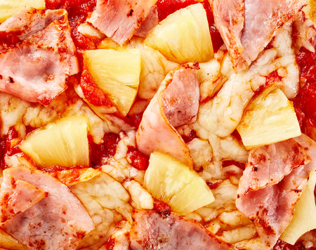 Delicious Hawaiian pizza topping background texture with pineapple and thinly sliced ham on melted mozzarella cheese viewed from above in close up detail