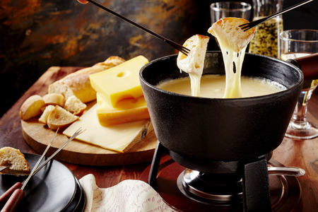 Gourmet Swiss fondue dinner on a winter evening with assorted cheeses on a board alongside a heated pot of cheese fondue with two forks dipping bread and white wine behind in a tavern or restaurant Standard-Bild