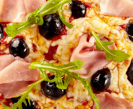Italian pizza topping detail with whole black olives, slivers of ham, fresh rocket and melted mozzarella cheese