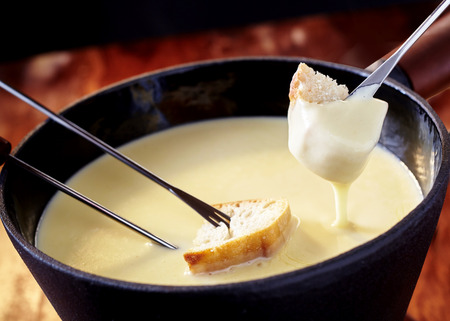 Close up on a pot of delicious Swiss cheese fondue with forks and bread being dipped into the mixture