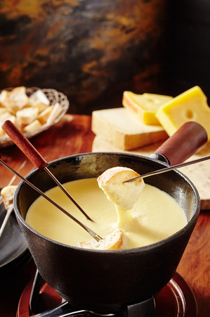 long handled: Dipping into a tasty cheese fondue with bread on long handled forks in a close up high angle view with copy space