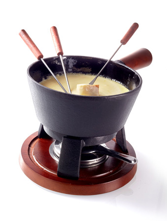 Isolated Swiss cheese fondue in a pot on a burner to keep the melted cheese and wine blend hot with long handled forks and bread for dipping Stock Photo
