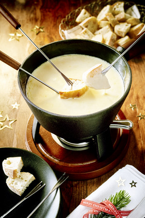 discreto: Tasty winter cheese fondue for Christmas with a high angle view of a pot of blended cheeses and wine over a burner with dipping forks and bread with discreet Xmas decorations and napkin Foto de archivo