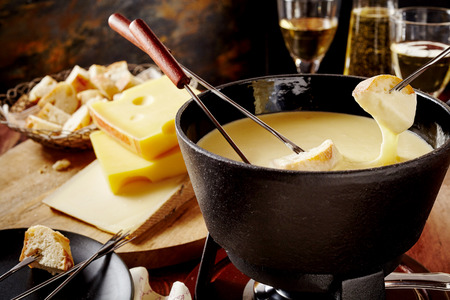 Speciality Swiss cheese fondue, a popular national dish made from a blend of assorted cheeses and wine served hot in a communal pot for dipping bread, with ingredient behind in a tavern or restaurant