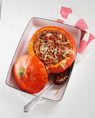 ovenbaked: Spicy stuffed autumn pumpkin with ground beef and melted cheese served in a dish for a hearty healthy meal