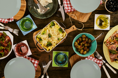 lunch table: Top down view on empty plates, cups, dish of baked pasta, vegetables, pizza and salad on table