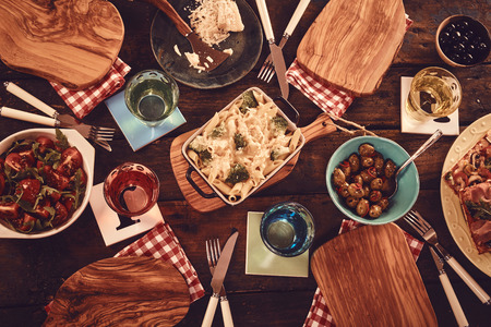 top down: Top down view on wooden plates with dishes of baked pasta, vegetables, olives and other ingredients