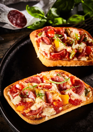 Toasted bread with a topping of melted cheese, basil, salami and sweet peppers served on a rustic round tray with ingredients behind