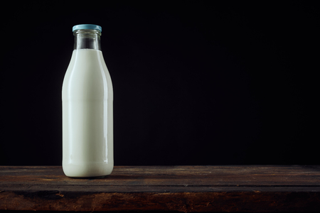 unlabelled: Full glass bottle of milk beside tall cup on wooden surface with copy space over dark background