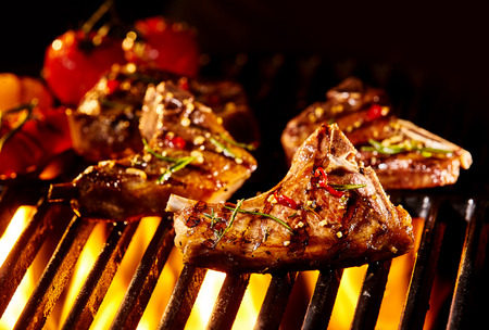 sizzling: Seasoned lamb cutlet pieces with bone being grilled under flames with roasted vegetables in background