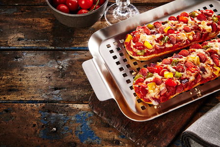 pepper salami: Gourmet homemade toasted baguette with trimmings topped with cheese, bell pepper, salami, basil and tomato for a wholesome snack on a rustic table