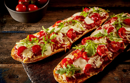 Grilled crispy crusty baguette topped with cherry tomatoes, cheese and fresh rocket served on a board on a rustic wooden table Stock Photo