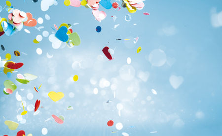Flying heart shaped confetti of red, yellow, green and blue colors floating around in sky with copy space Stock Photo