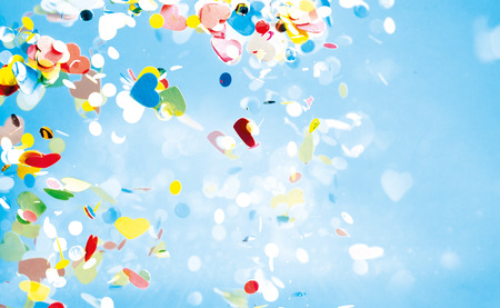 fasching: Flying confetti of red, yellow, green and blue colors floating around in sky with copy space Stock Photo