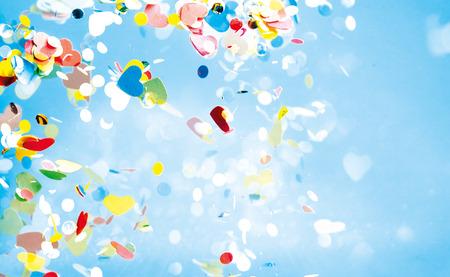 Vliegende confetti van rode, gele, groene en blauwe kleuren rondzweven in de hemel met een kopie ruimte Stockfoto