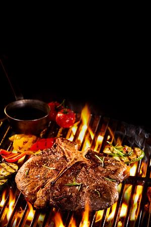 Хорошо сделанный T кости стейк на пылающий гриль для барбекю с жареными овощами, маслом и копией пространства Фото со стока