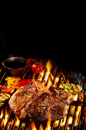 Well done T bone steak on flaming barbecue grill with roasted vegetables, oil and copy space