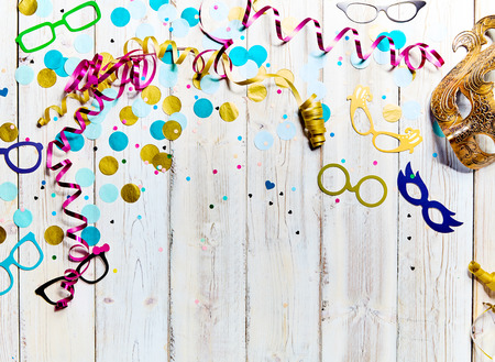 white party: Party or carnival background with copy space with scattered streamers, confetti, fun colorful eyeglasses frames and a mask forming a border over white wood