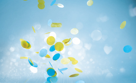 Colorful yellow and blue shapes falling or floating around in blue sky background