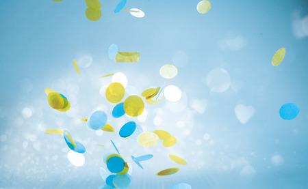 Formes jaunes et bleus colorés tombant ou flottant sur fond de ciel bleu Banque d'images