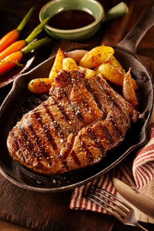 Grilled beef with potato wedges in oval shaped cast iron plate with carrots and oil in background