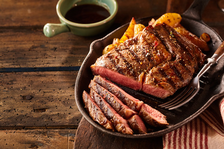 Cast iron plate with sliced grilled rib-eye steak on table with yellow potato wedges and oil in saucer over table with copy space Imagens