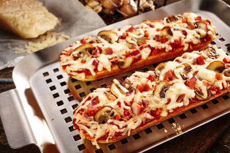 Tasty grilled baguettes with mushroom, tomato and melted grated cheese on a stainless steel grill pan with ingredients behind