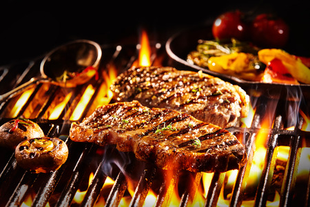 Grilled pieces of delicious rump steak garnished with herbs and sauce alongside mushrooms and vegetables over flames 스톡 콘텐츠