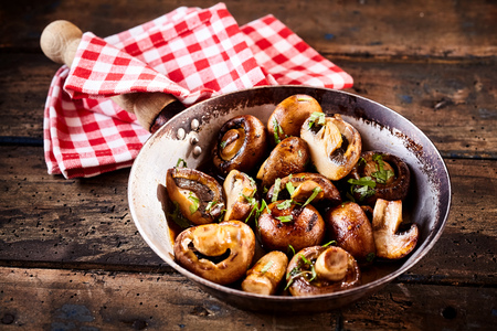 button mushroom: Whole crimini mushrooms in stir fry pan with checkered red and white napkin around the handle