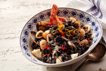 Single serving of seafood risotto named nero specialty dish with shrimp and scallops smothered in ink from squid Stock Photo