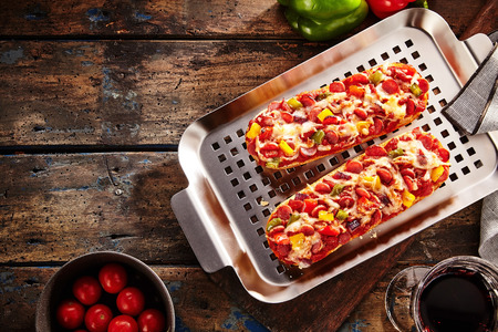 red pepper: View from above of a stainless steel grill pan with two crusty baguettes with generous assorted toppings and sliced salami on a rustic wooden table with copy space Stock Photo