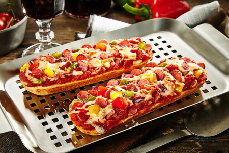 glass topped: Grill pan with gourmet toasted baguettes topped with salami, sausage, basil, bell pepper, tomato and cheese served with a glass of red wine to the side
