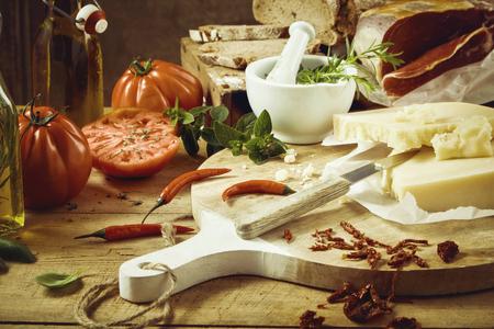 Tema de la comida culinaria con carne en rodajas, pimientos, queso amarillo duro, pan casero, tomates gourmet y aceite de oliva con cuchillo en la tabla de cortar Foto de archivo
