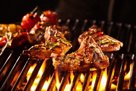 carne asada: Condimentadas deliciosas piezas de carne de cordero chuleta con hueso está a la parrilla bajo las llamas con verduras asadas en el fondo