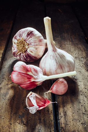 pungent: Two whole garlic bulbs beside cloves on old wooden table for theme about pungent herbs for cooking and health