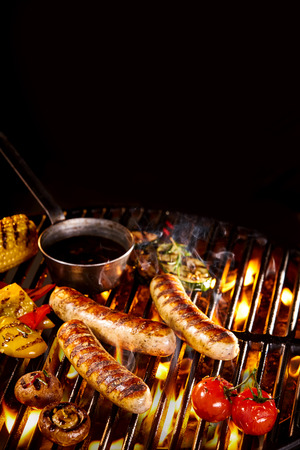 sizzling: Grilled sausages besides peppers and tomatoes with small steel pan of oil on hot flaming grill