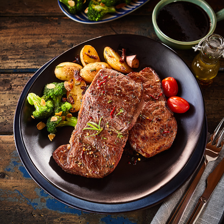 Top down view on oblong shaped plate with steak dinner. Includes side servings of broccoli, grilled potatoes and grape tomatoes. Standard-Bild