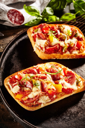 appetizers: Two square shaped pizza appetizers topped with pepperoni slices, cheese and herbs on cast iron pan Stock Photo