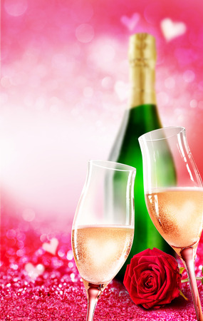 sweethearts: Romantic champagne glass and bottle theme with sparkling pink background. Rose flower and heart shapes at top and bottom. Stock Photo
