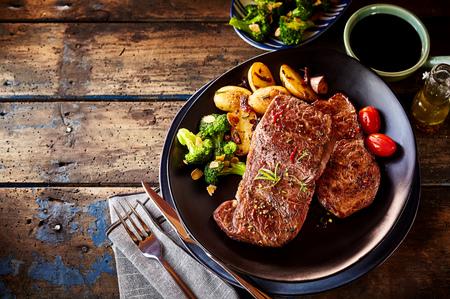 トップダウン ビュー グリル ステーキ、ポテト、トマト、オイルの受け皿の横にあるテーブルの上の野菜のディナーに