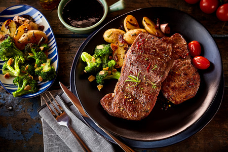 Top down view on steak pieces with vegetable side dish of broccoli, tomatoes and potatoes