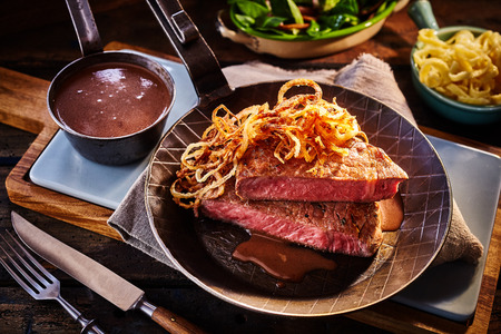 onion: Setting of rare cooked prime rib with onions on top and side of gravy, green leaf lettuce salad and peppers Stock Photo