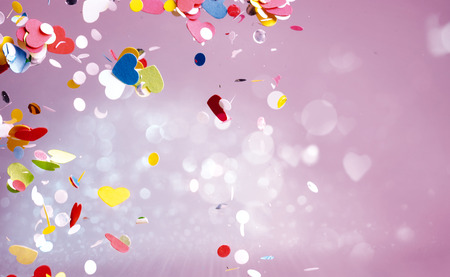 Floating confetti of red, yellow, green and blue colors floating around in purple background with copy space