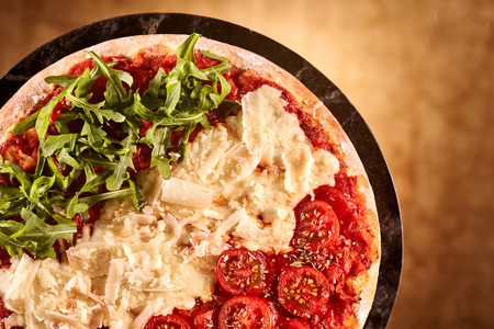 ambiente: Lettuce, cheese and tomatoes on pizza over pan with obscured brown background