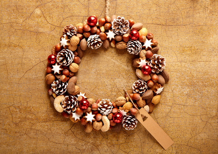 christamas: Cute wreath made of nuts and pine cones over brown crackled background with copy space