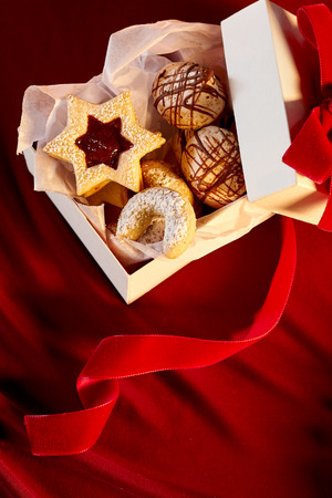 biscuits: Top down view of open white cardboard cookie box filled with star shaped and round sweet biscuits