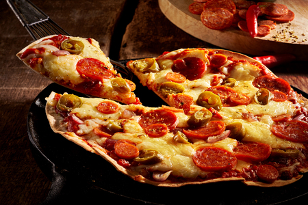 ovenbaked: Tasty crispy oven-baked tortilla pepperoni pizza with spicy Italian sausage, melted cheese and tomato with a single slice being served in a restaurant, close up view Stock Photo