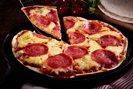 Slice of tasty salami and cheese tortilla pizza being served in a rustic kitchen with a closeup view on the whole pizza on an old plate