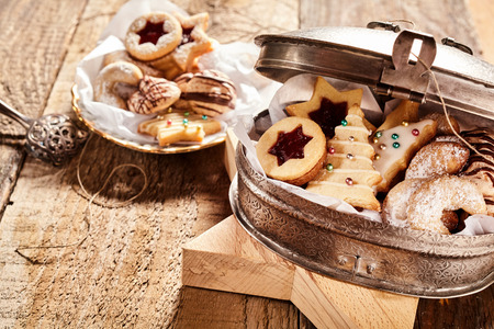 Half open cookie container with latch filled with various Christmas themed treats over wood background Stock Photo